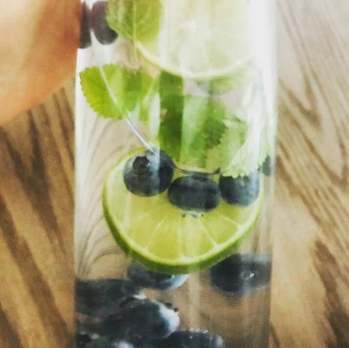 Bicchiere contenente acqua, mirtilli, foglie di menta e lime