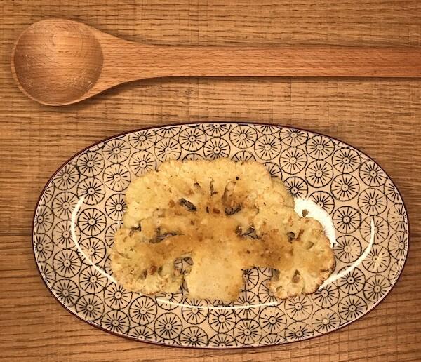 Cavolfiore dopo cottura servito su piatto ovale accompagnato da cucchiaio in legno