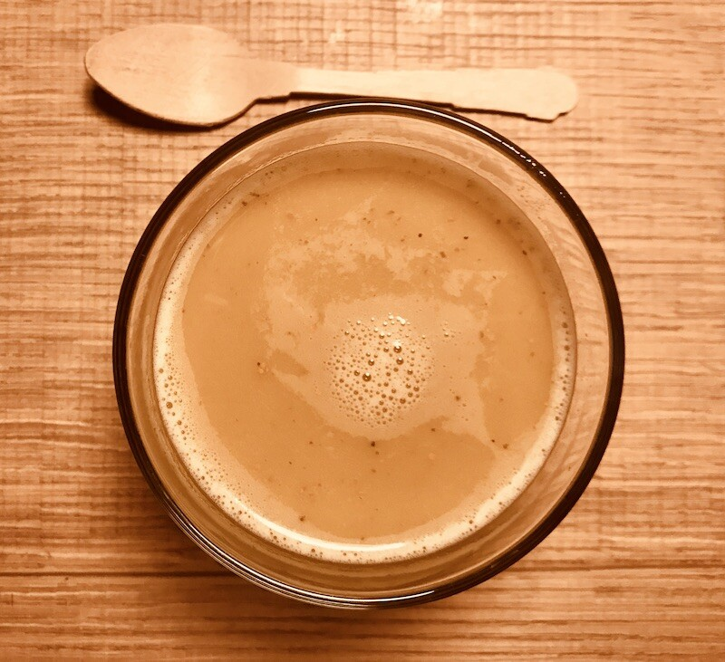 Tazza in vetro di golden milk e cucchiaio di legno
