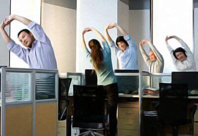 A group of employees doing exercises at their desk in office