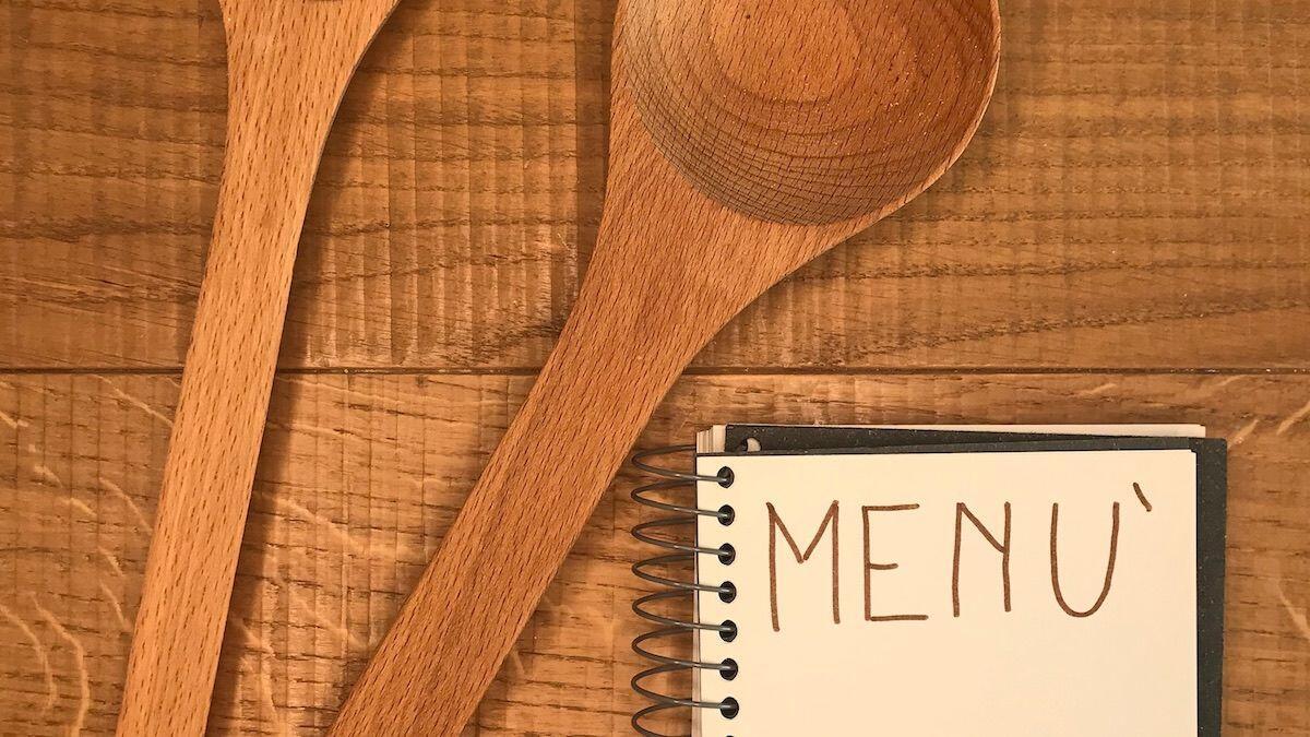 Due cucchiai in legno che rappresentano thewealthyspoon ed il menù di un ristorante, suggerimenti per mangiare fuori casa della Nutrizionista Dott.ssa Paola Proietti Cesaretti
