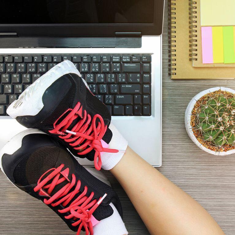 Feet wearing runners over a laptop over an office desk
