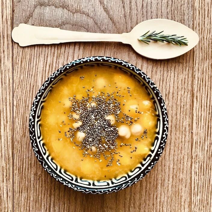 Ciotola decorata contenente zuppa di ceci e zucca accompagnata da rametto di rosmarino su cucchiaio di legno